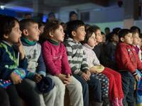 "Children attend a film screening as part of the mobile cinema ""Komina Film"" initiative organised by Syrian-Kurdish filmmaker Shero Hinde, at a school yard in the village of Shaghir Bazar, 55 kilometres southest of Qamishli in the Kurdish-populated areas of northeastern Syria's Hasakeh province, on July 28, 2019. (Twitter)"