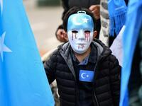 Boy wears mask with tears of blood during recent protest of ethnic Uighurs in Brussels asking EU to pressure China to close 're-education centres' (AFP/file photo)