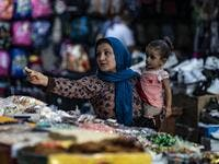 A woman pays a merchant at a market in the Kurdish-majority city of Qamishli in northeast Syria.  Delil SOULEIMAN / AFP