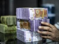 A merchant arranges stacks of Syrian pounds at a market in the Kurdish-majority city of Qamishli in northeast Syria on September 10, 2019. The declining value of the pound is a sure sign of Syria's ailing economy. The civil war has battered the country's finances and depleted its foreign reserves. A flurry of international sanctions on President Bashar al-Assad's regime and associated businessmen since the start of the war in 2011 has compounded the situation.  Delil SOULEIMAN / AFP