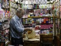 A merchant prepares lunch inside his shop at the Bzourieh market in the centre of the Syrian capital Damascus . The declining value of the pound is a sure sign of Syria's ailing economy. LOUAI BESHARA / AFP