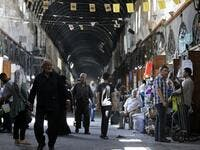 Shoppers walk through the Bzourieh market in the centre of the Syrian capital Damascus. LOUAI BESHARA / AFP