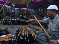 In this photo taken on September 15, 2019, chefs prepare long kebabs made from minced meat ahead of a traditional feast held for a marriage ceremony in Kashmir's Baramulla district, north of Srinagar. TAUSEEF MUSTAFA / AFP