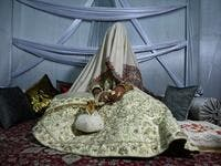 In this photo taken on September 15, 2019, a bride with her face and body covered with a shawl sits in her new husband's home following their marriage in Kashmir's Baramulla district, north of Srinagar. TAUSEEF MUSTAFA / AFP