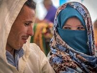"A young Amazigh (Berber) couple smile at each other as they wait for their wedding ceremony during the annual ""Engagement Moussem"" festival near the village of Imilchil in central Morocco's high Atlas Mountains on September 21, 2019. Each year in the High Atlas Mountains hamlet of Ait Amer, tribes celebrate with dances and music, the collective wedding of young Amazigh couples during the traditional festival of ""Engagement Moussem"". FADEL SENNA / AFP"
