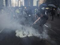 A protester pours water on a tear gas cannister fired by police beside the Admiralty MTR station in Hong Kong on October 1, 2019, as the city observes the National Day holiday to mark the 70th anniversary of communist China's founding. Mark RALSTON / AFP