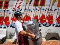 A volunteer carries empty pots at a Chinese shrine during the annual Vegetarian Festival in Phuket on October 5, 2019. Mladen ANTONOV / AFP