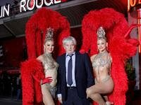 Moulin Rouge cabaret CEO Jean-Jacques Clerico (C) poses with French dancer Mathilde (L) and Australian dancer Rhylee (R) during the celebration of the 130th anniversary of the French oldest cabaret, on October 6, 2019 in Paris.  GEOFFROY VAN DER HASSELT / AFP
