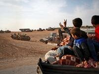 Syrian Arab civilians flash the victory sign as Turkish armoured personnel carriers and US-made M60 taks gather in the village of Qirata on the outskirts of the northern Syrian city of Manbij near the Turkish border, on October 14, 2019. (AFP/ File Photo)
