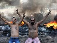 Lebanese demonstrators gesture as tires burn during a protest against dire economic conditions in the industrial zone of Dora on the northern outskirts of Beirut (AFP)