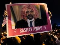 "A Lebanese protester lifts a picture of Prime Minister Saad Hariri in a wig during a rally in downtown Beirut on the third day of demonstrations against tax increases and official corruption, on October 19, 2019. The writing ""sashay away"" refers to a catchphrase from a drag queen TV show meaning ""leave"". IBRAHIM AMRO / AFP"