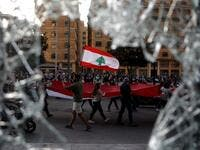 Lebanese demonstrators waving a national flag as they take part in a protest in the capital Beirut's the downtown district (AFP)