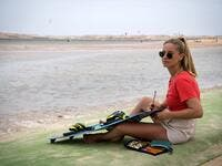 A picture taken on October 10, 2019, shows a kitesurfer fixing her board at Dakhla beach in Morocco-administered Western Sahara. In the heart of disputed Western Sahara, a former garrison town has become an unlikely tourist magnet after kitesurfers discovered the windswept desert coast on the Atlantic is perfect for their sport. FADEL SENNA / AFP