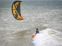A picture taken on October 10, 2019, shows a kitesurfer riding waves at Dakhla beach in Morocco-administered Western Sahara. In the heart of disputed Western Sahara, a former garrison town has become an unlikely tourist magnet after kitesurfers discovered the windswept desert coast on the Atlantic is perfect for their sport. FADEL SENNA / AFP