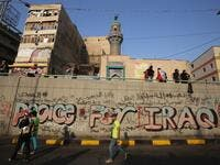 Iraqi demonstrators walk by a graffiti-filled wall in Tahrir square in the capital Baghdad on November 3, 2019, amid ongoing anti-government protests. Protesters in Iraq's capital and the country's south shut down streets and government offices in a new wave of civil disobedience, escalating their month-long movement demanding wholesale change of the political system. AHMAD AL-RUBAYE / AFP