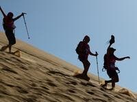 "Women run down a sand dune as they take part in the desert trek ""Rose Trip Maroc"", on November 4, 2019 in the erg Chebbi near Merzouga. The Rose Trip Maroc is a female-oriented trek where teams of three must travel through the southern Moroccan Sahara desert with a compass, a map and a topographical reporter. JEAN-PHILIPPE KSIAZEK / AFP"