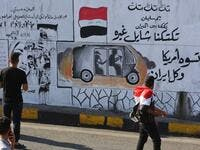 "Iraqis walk past graffiti hailing Iraq's tuk-tuk drivers who have been helping protesters in Baghdad's Tahrir square, as the Iraqi capital braces for another day of protests on November 6, 2019. Arabic slogans on the wall read: ""Our Tuk-tuk drivers are in the fire, they help others.. they are better than America and Iran together."" The drivers of the motorised rickshaws, typically seen in poorer parts of the capital, have become the unofficial heros of the protest movement. SABAH ARAR / AFP"