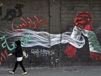 A woman walks past a graffiti drawn on the wall of a building at the al-Nour Square in the northern port city of Tripoli on November 7, 2019. An unprecedented protest movement has gripped Lebanon since October 17, demanding an overhaul of a political class that has remained largely unchanged since the end of the country's 1975-1990 civil war. In the northern city of Tripoli, where mobilisation has been relentless since the protests erupted on October 17, demonstrators took down politicians' portraits from c
