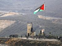 A picture taken from the Israeli side of the border shows King Abdullah II of Jordan (L) standing to attention with army troops under a Jordanian national flag during a ceremony at the Jordan Valley site of Naharayim, also known as Baqura, east of the Jordan River on November 11, 2019. (AFP/ File Photo)