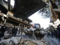 Syrian municipality workers clearing debris from building in Damascus' Mazze neighbourhood following an air strike (AFP)