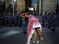 A Lebanese protester draped in a traditional Palestinian Keffiyeh scarf walks past a row of security forces during ongoing anti-government demonstrations in central Beirut  (AFP)