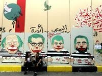 Anti-government protesters sit under graffiti depicting Lebanese politicians with joker faces sprayed on a wall in downtown Beirut on November 12, 2019. Banks and schools in Lebanon were closed today as protesters tried to prevent employees from clocking in at state institutions nearly one month into an anti-graft street movement. Unprecedented protests erupted across Lebanon on October 17, demanding the ouster of a generation of politicians seen by demonstrators as inefficient and corrupt.  JOSEPH EID / AF