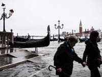"People walk across the Ponte della Paglia bridge, past a stranded gondola after an exceptional overnight ""Alta Acqua"" high tide water level, early on November 13, 2019 in Venice. Powerful rainstorms hit Italy on November 12, with the worst affected areas in the south and Venice, where there was widespread flooding. Within a cyclone that threatens the country, exceptional high water were rising in Venice, with the sirocco winds blowing northwards from the Adriatic sea against the lagoon's outlets and prevent"
