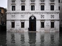 "A man stands by the entrance of the Palazzo Patriarcale on the flooded Piazza dei Leoncini square after an exceptional overnight ""Alta Acqua"" high tide water level, early on November 13, 2019 in Venice. Powerful rainstorms hit Italy on November 12, with the worst affected areas in the south and Venice, where there was widespread flooding. Within a cyclone that threatens the country, exceptional high water were rising in Venice, with the sirocco winds blowing northwards from the Adriatic sea against the lago"