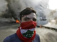 A Lebanese protester stands in front of burning tyres and debris in the area of Jal el-Dib, on the northern outskirts of the Lebanese capital Beirut, on November 13, 2019. A man was shot dead south of Beirut after the army opened fire to disperse protesters blocking roads, Lebanese state media said, nearly a month into an unprecedented anti-graft street movement. JOSEPH EID / AFP