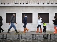 "People walk on a footbridge across a flooded street after an exceptional overnight ""Alta Acqua"" high tide water level, on November 13, 2019 in Venice. Venice was hit by the highest tide in more than 50 years late November 12, with tourists wading through flooded streets to seek shelter as a fierce wind whipped up waves in St. Mark's Square. Marco Bertorello / AFP"