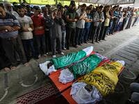 Palestinian mourners pray over the bodies of Rafat Ayad and his two sons Amir and Islam on during a funeral in Gaza City on November 13, 2019. Exchanges of fire triggered by Israel's targeted killing of a top militant in Gaza raged for a second day and showed little sign of easing, with 22 Palestinians killed. Fresh rocket barrages were fired at Israel, which responded with strikes on what it said were Islamic Jihad militant sites and rocket-launching squads in the Gaza Strip.  MAHMUD HAMS / AFP