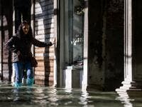 A woman carefully walks across a flooded arcade on November 14, 2019 in Venice. Much of Venice was left under water after the highest tide in 50 years ripped through the historic Italian city, beaching gondolas, trashing hotels and sending tourists fleeing through rapidly rising waters. Filippo MONTEFORTE / AFP