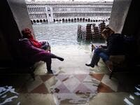 People sit on benches in a flooded arcade by St. Mark's Square on November 15, 2019 in Venice, two days after the city suffered its highest tide in 50 years. Flood-hit Venice was bracing for another exceptional high tide on November 15, as Italy declared a state of emergency for the UNESCO city where perilous deluges have caused millions of euros worth of damage. Filippo MONTEFORTE / AFP