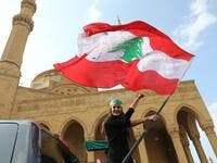 A Lebanese anti-government protester waves the national flag as she prepares to head to the south of Lebanon on a 'revolution' bus from central Beirut on November 16, 2019. ANWAR AMRO / AFP