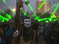 A demonstrator wearing Guy Fawkes mask gestures during a protest against the government, in Santiago on November 18, 2019. (AFP/ File Photo)