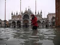 Submerged: A woman crosses the flooded St Mark's Square yesterday morning where Venice's 1,200-year-old basilica (pictured behind her) was flooded by the high tide. (AFP/ File Photo)