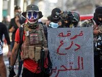 "A 23-year-old unemployed Iraqi man, wearing face-paint modeled after DC comic book and film character ""The Joker"", poses for a picture with a makeshift riot shield bearing text in Arabic reading ""Tahrir Shield Division"", during an anti-government demonstration in the capital Baghdad on November 22, 2019. (AFP/ File Photo)"
