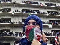 "A woman covers her face with the national flag, as Algerian protesters demonstrate in the capital Algiers against ailing president's bid for a fifth term on March 8, 2019. Tens of thousands protested across Algeria today in the biggest rallies yet against ailing President Abdelaziz Bouteflika's bid for a fifth term, despite the defiant leader's warning of the risk of ""chaos"". RYAD KRAMDI / AFP"