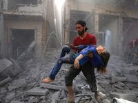 A man evacuates a young bombing casualty after a reported air strike by regime forces and their allies in the jihadist-held Syrian town of Maaret Al-Noman in the southern Idlib province, on May 26, 2019. (AFP/ File Photo)