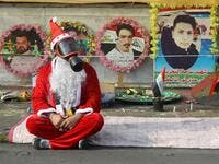 An Iraqi demonstrator wearing a Santa Claus costume and a gas mask sits on a blanket in the capital Baghdad's Tahrir Square, amid ongoing anti-government protests, on December 6, 2019.  (AFP/ File Photo)