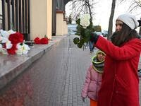 A woman with her daughter lay flowers outside the Canadian Embassy in Kiev on January 8, 2020 in remembrance of the victims of the Ukraine International Airlines Boeing 737-800 crash in the Iranian capital Tehran. A Ukrainian airliner carrying 176 people from seven countries crashed shortly after takeoff from Tehran on January 8, 2020 killing all on board. The vast majority of the passengers on the Boeing 737, which had been flying from Tehran to Kiev for Ukraine International Airlines, were Iranians and Ca
