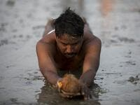 A Hindu devotee performs a ritual before taking a holy dip in the Bay of Bengal during the Gangasagar Mela, at Sagar Island, around 150 kms south of Kolkata on January 13, 2020. XAVIER GALIANA / AFP
