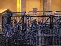 Anti-government protesters attempt to break through the security barrier in the central downtown district of the Lebanese capital Beirut near the parliament headquarters during clashes with security forces on January 18, 2020. ANWAR AMRO / AFP