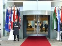 Guards stand next to the flags of the participating countries at the entrance of the German Chancellery in Berlin on January 19, 2020, before the arrival of the participants of the Peace summit on Libya. John MACDOUGALL / AFP