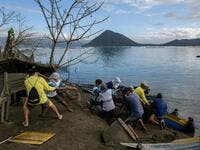 A group of fishermen haul a boat from the water as they make repairs to their operations affected by the eruption of the Taal volcano, in Buso Buso on January 20, 2020. Ed JONES / AFP