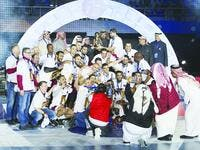 HE Sheikh Joaan bin Hamad al-Thani, the president of the Qatar Olympic Committee, poses with Qatar Handball Association president Ahmed Mohamed al-Shabi and members of the Qatar national team after they won the Asian Handball Championship.