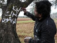 "A Syrian man writes in white paint on the trunk of a tree the Arabic slogan ""we will not abandon the olives"", near the frontline between Syrian government forces and Turkish-backed opposition fighters in the town of Sarmin in the northern Syrian Idlib province on February 4, 2020. Omar HAJ KADOUR / AFP"