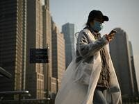 People wearing protective face masks walk on an overpass in Shanghai on February 24, 2020. China is expected to decide February 24 whether to postpone its annual parliament session for the first time since the Cultural Revolution as the country battles the COVID-19 coronavirus outbreak. Noel Celis / AFP