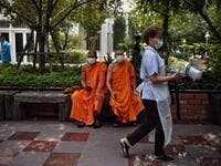 Monks wearing face masks sit outside a temple while a worker carries materials for use to disinfect the Wat Pak Nam Buddhist temple, as part of measures against the COVID-19 novel coronavirus, in Bangkok on March 16, 2020. Lillian SUWANRUMPHA / AFP
