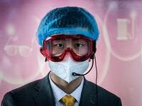 A worker at an information desk wearing protective gear as a preventive measure against the COVID-19 coronavirus looks on at a nearly empty arrivals area at Beijing Capital Airport in Beijing on March 16, 2020. China tightened quarantine measures for international arrivals as the country worries about a rise in imported cases of the deadly coronavirus and anger rages online at how Europe and the United States are handling the pandemic. NICOLAS ASFOURI / AFP